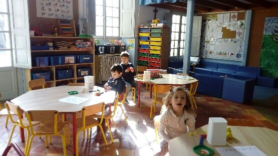 Sur cette photo on voit trois enfants dans une salle de classe