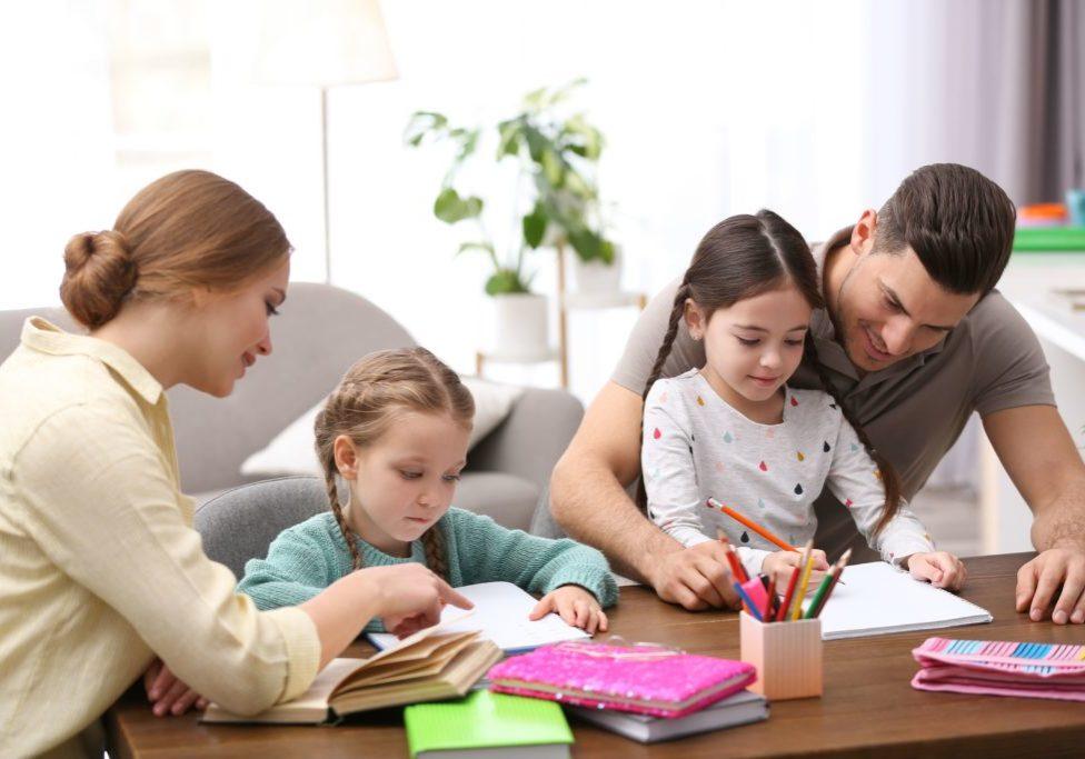 On voit sur cette photo deux parents qui aident leurs deux filles à faire leurs devoirs